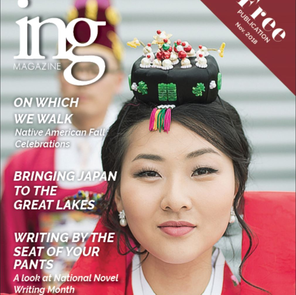 A magazine front cover featuring a young man and woman in traditional Korean attire.