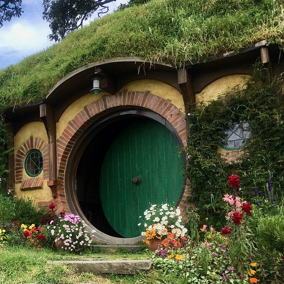 A hobbit hole with a green door and flowers growing around it.