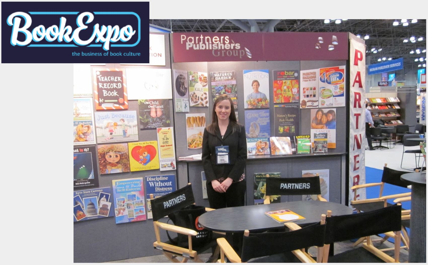 An office professional standing at a conference booth with books behind them.